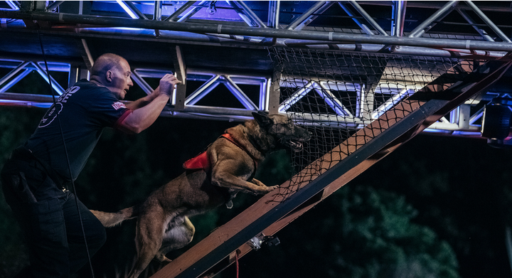 "A K-9 team navigates the challenging Fire Escape. ""America's Top Dog"" worked with some of the top K-9 units in the country as well as certified training organizations during the casting process. (Photo: A&E) -"