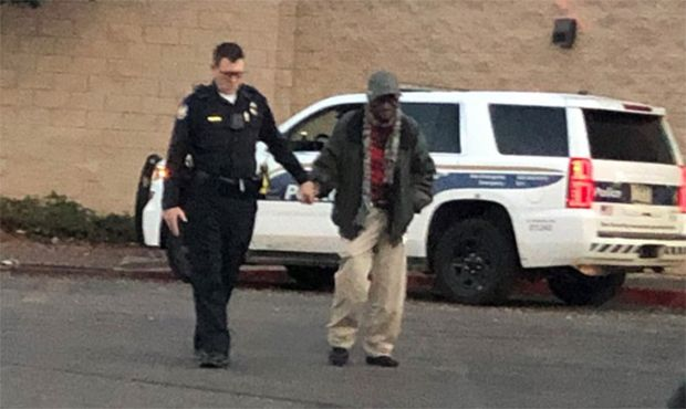 Phoenix Officer Joseph Mayfield assists an elderly man outside of a local shopping mall. A citizen snapped the photo and shared it on social media. (Photo: Phoenix PD/Twitter) -
