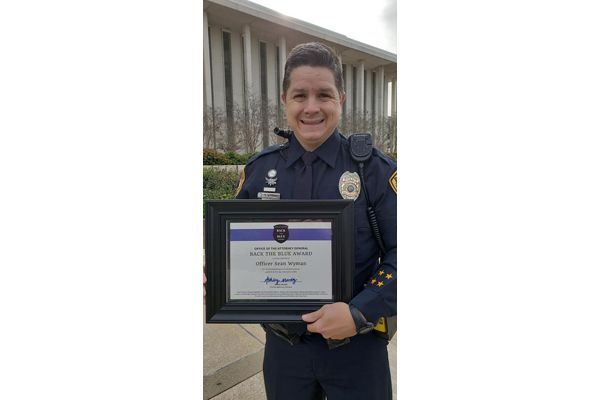 "Officer Sean Wyman was presented with the Attorney General's ""Back the Blue"" award for his efforts to help police officers in distress seek help and prevent suicides. - Image courtesy of Tallahassee Police Department / Facebook."