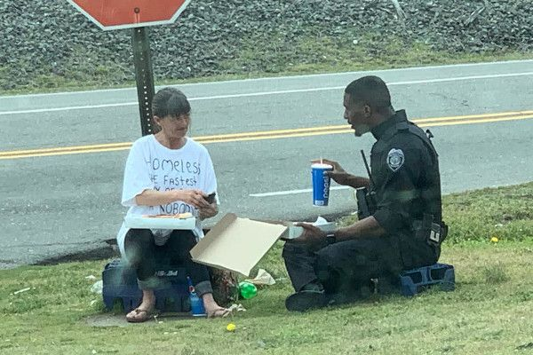 A Goldsboro (NC) Police Department officer shares a pizza lunch with a homeless woman. - Photo: Chris Barnes / Facebook