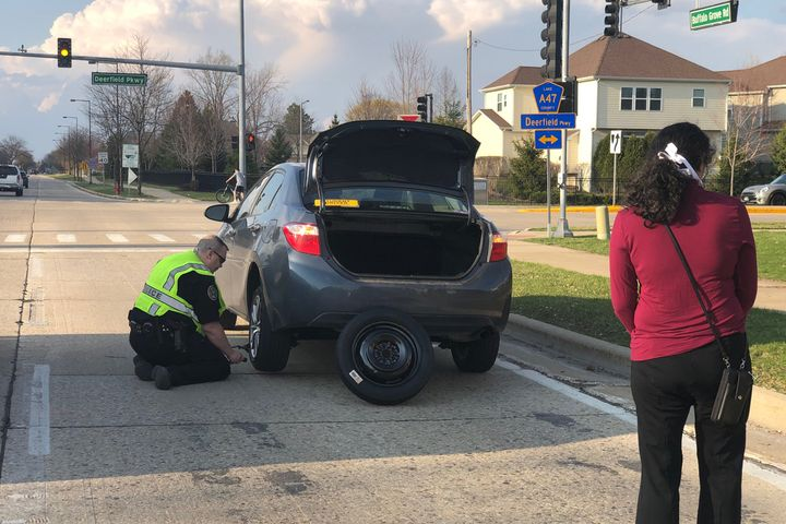 An officer with the Buffalo Grove (IL) Police Department was recently seen in an image posted to social media helping a stranded motorist change the tire on her vehicle. - Image courtesy of Buffalo Grove PD / Facebook.