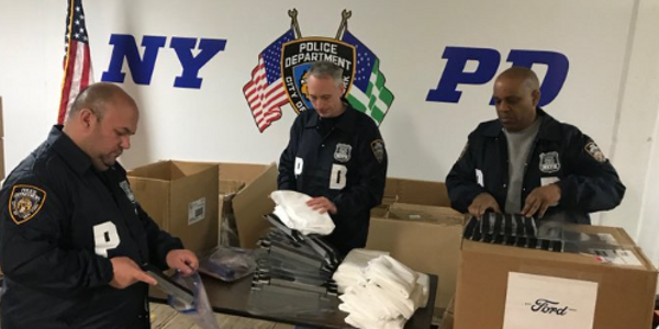 NYPD officer open a shipment of coronavirus face shields from Ford. (Photo: Ford)