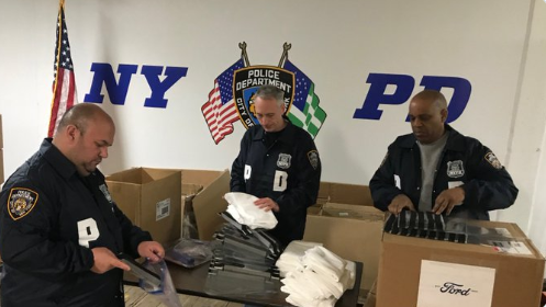 NYPD officer open a shipment of coronavirus face shields from Ford. (Photo: Ford) -