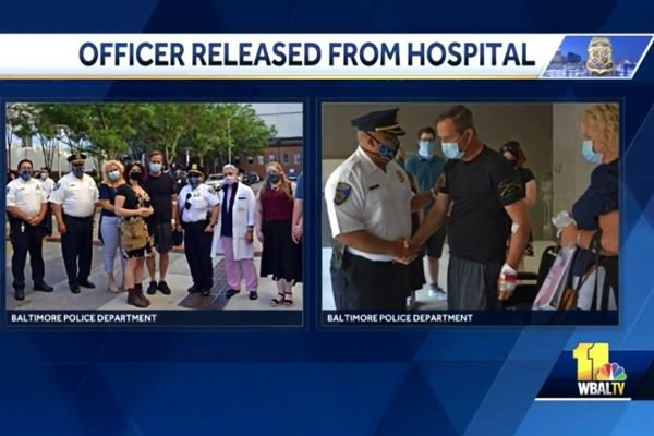 Officer Brian Burke was greeted outside the hospital by his family, dozens of fellow officers, and a group of civilian police supporters as he got into a vehicle and made his way home to recover from his wounds. - Screen grab of news reportby NBC News.