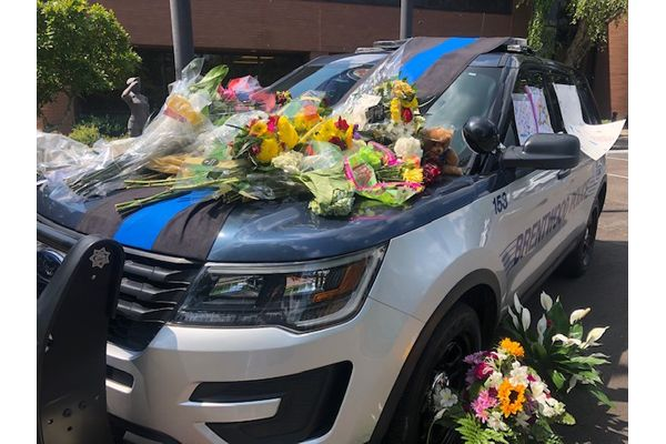 A candlelight vigil was held over the weekend for Officer Legieza, and citizens from the community have left flowers and memorials on a squad car parked in front of the police station in the days following his death. - Image courtesy of Brentwood Police Department / Facebook.