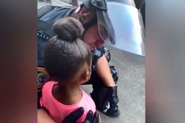An officer with the Houston Police Department was captured on cell phone video comforting a 5-year-old girl during a protest last week. - Screen grab of news report.