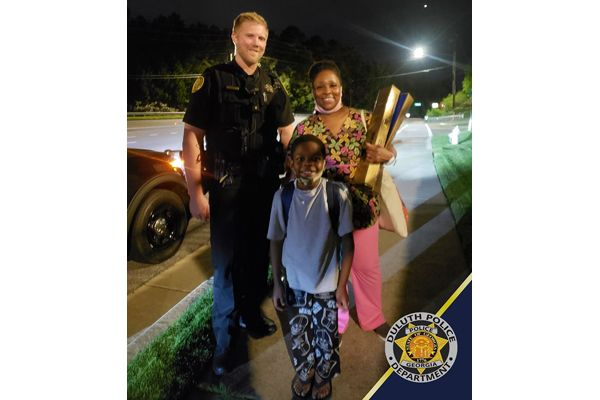 An officer with the Duluth (GA) Police Department who had come upon a woman and child walking down a rural road early Tuesday morning made a call to a car service so that they could safely get to a relative's house after their car broke down. - Image courtesy of Duluth Police Department / Facebook.