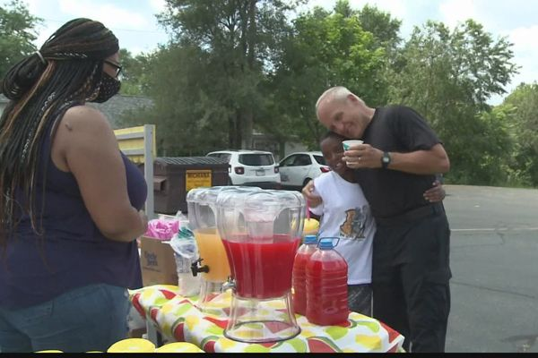 An officer with the South Bend (IN) Police Department was seen over the weekend helping two boys—a 12-year-old and his four-year-old brother—serving refreshments of lemonade, punch, and popcorn to area residents. - Screen grab of news report.