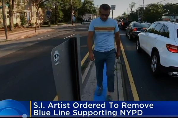 An artist and activist who is a supporter of law enforcement officers recently painted a blue line in front of a police precinct house on Staten Island in New York. Now he's been told by city attorneys representing the Department of transportation that he must remove the paint and restore the pavement to its original condition.    - Screen grab of news report.
