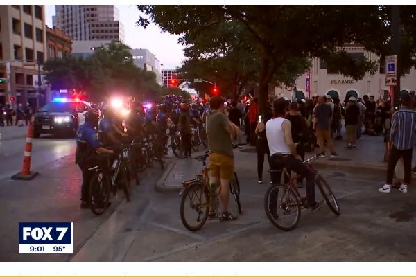 During protests over the in-custody death of George Floyd in May, officers in Austin (TX) have used bicycles to block people in the crowd from getting onto roadways, and now the bike shop that had had the contract to sell and service those bicycles has cancelled its contract with the department. - Screen grab of news report.