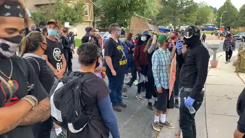 Protesters march outside the home of a Colorado Springs officer who was cleared in a fatal shooting that happened 12 months ago. (Photo: Screen Shot from Gazette Video) -