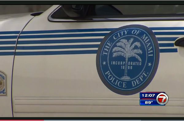 The wife of an officer with the Miami Police Department perished in the back of her husband's squad car on Friday afternoon as the vehicle's temperature rose to dangerous levels and she had no way of getting out. - Screen grab of news report.