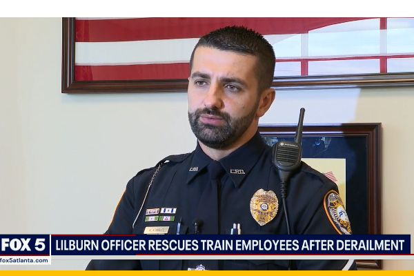 Officer Almedin Ajanovic was finishing an off-duty job early Sunday morning when he heard calls about explosions and a train derailment. He raced to the scene and immediately took action to save the lives of the engineers trapped on top of the toppled train. - Screen grab of news report.