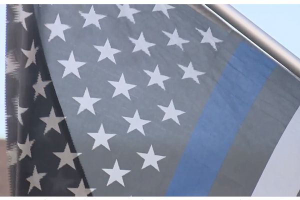 """An officer in Colorado has been ordered by his Home Owners Association (HOA) to remove from his doorstep a """"Thin Blue Line"""" flag displayed in support of law enforcement. - Screen grab of news report."""