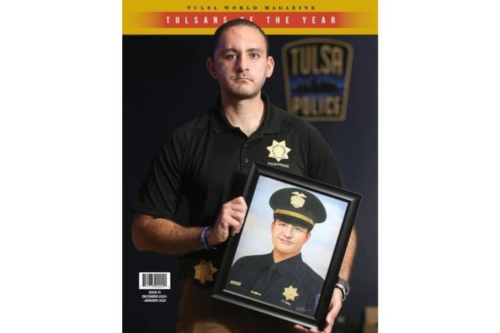 Cover photo of the Tulsa World magazine shows Officer Aurash Zarkeshan holding a portrait of his slain supervisor Sgt. Craig Johnson. Both men have been honored as Tulsans of the year. (Photo: Tulsa World) -