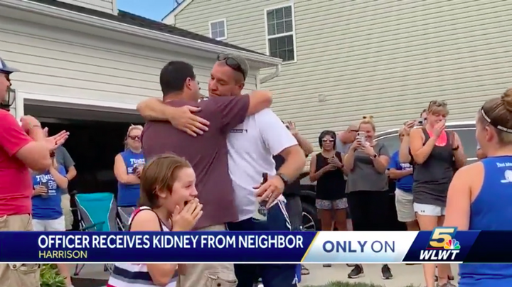 Green Township, OH, police officer Troy Biggs (white shirt) hugs his neighbor after finding out the man would be his kidney donor. (Photo: WLWT Screen Shot) -