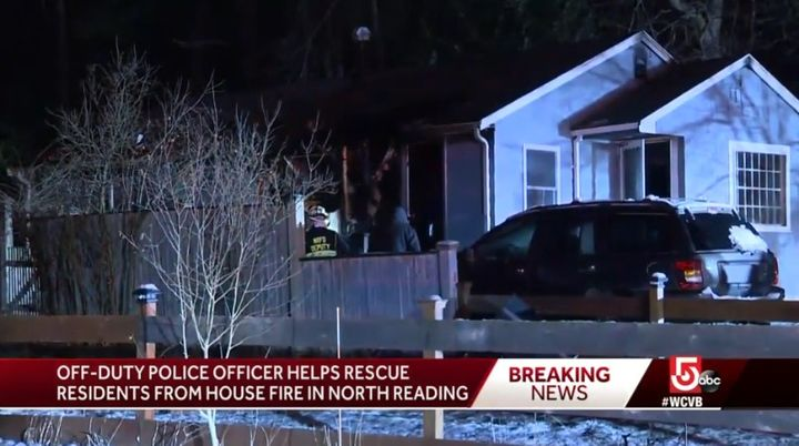 An off-duty North Reading, MA, officer saw this house on fire and had to kick in the door to alert the residents. (Photo: WCVB screen shot) -