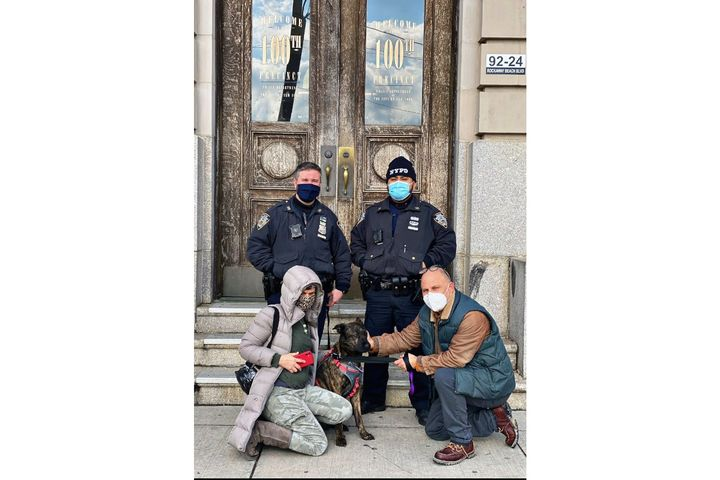Members of the NYPD Harbor team that rescued Tinkerbell pose with the dog and his owners. (Photo: NYPD) -