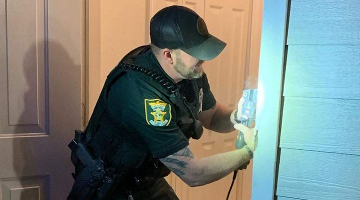 After clearing the residence, Deputy Lewis wanted to make sure the family felt safe for the rest of the night, so he grabbed some tools and bought some supplies to repair the damage to the doorway. (Photo: St. Johns County SO/Facebook) -