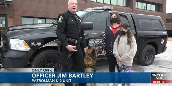 Officer Jim Brantley with 11-year-old Izzy Greenfelder, her mother Brandi, and K-9 Max in his...