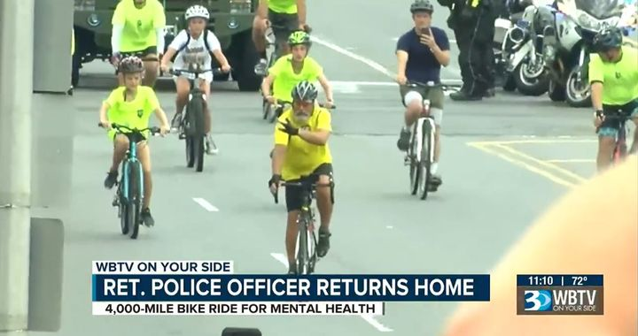 Retired Sergeant Christopher Lowrance arrives home in North Carolina after bicycling from Oregon to raise awareness of police suicide. (Photo: WBTV Screen Shot) -