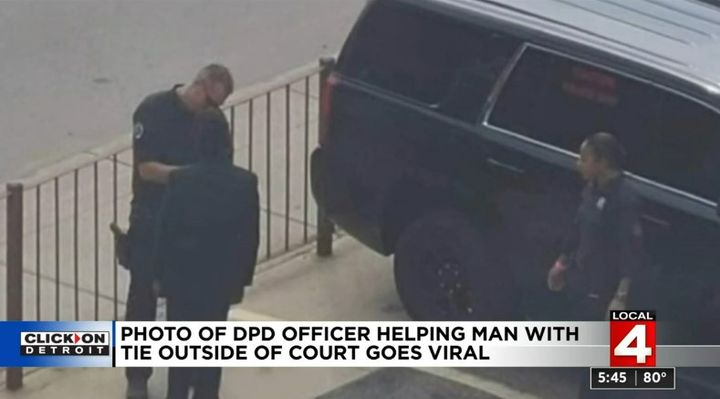 Cpl. Eric O'Neal is a K-9 unit officer with the Detroit Police Department but recently he became a dresser, helping a young man tie his necktie. (Photo: ClickonDetroit Screen Shot) -