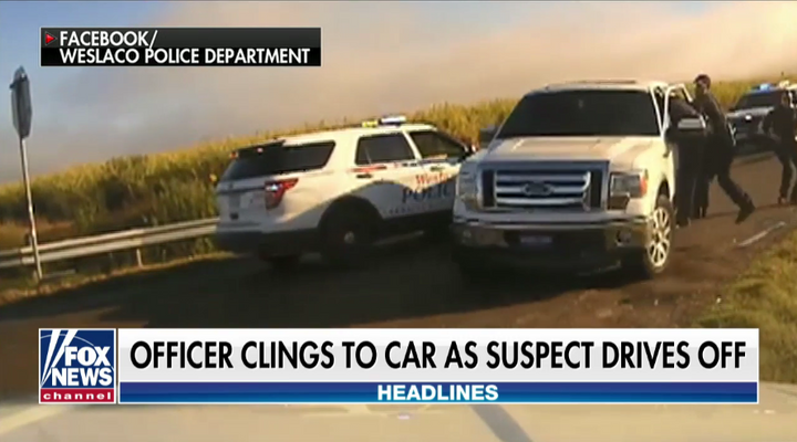 A Welasco, TX, police officer clings to a pickup truck as a motorist flees a traffic stop Sunday. (Photo: Fox News Screen Shot)