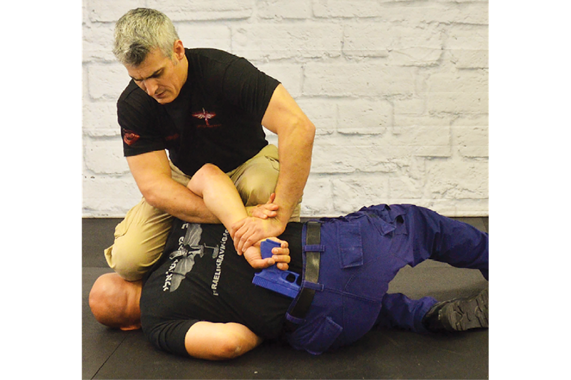 Drop with him, landing your left knee at his elbow and your right knee briefly on his head.