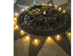 Emblem at the middle of the Memorial. The flowers and candles were placed on May 13 for the...