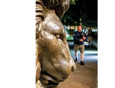 Michael McCann of the Virginia State Police plays his bag pipes as he approaches the lion at the...