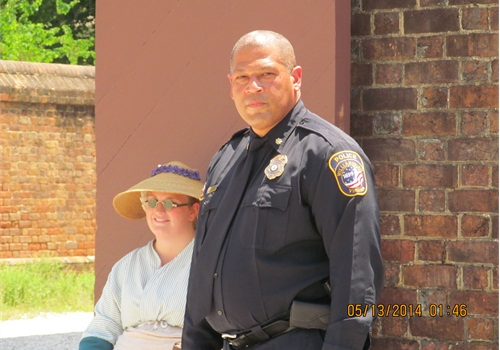 "Lt. Greg Riley of the Williamsburg PD at the Magazine: ""They're great, we work hand in hand with them,"" says Valerie Miller, a Foundation employee dressed in the period gown on this 90 degree day outside of the Magazine, the arsenal where the colony once stored its gunpowder, flints, tents and tools. ""We see [the police] walking around, even at church functions, and say hi."" (Photo: Kristine Meldrum Denholm)"