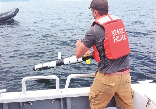 A state police officer launches the Ocean Server Technology Iver3-580 submersible robot. The Iver features side scan sonar and can operate at depths of up to 200 meters. Photo via Ocean Server