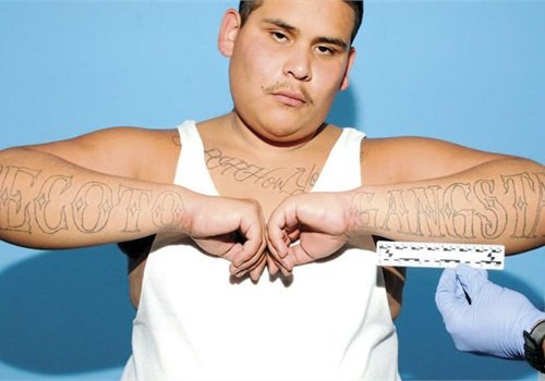 "Andrew Barrientos shows off his forearm gang tattoos ""DeCoto"" and ""Gangsta."" Photo: Alameda County D.A."