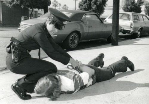 A female police officer makes an arrest in the 1980s. Photo courtesy of Los Angeles Police Historical Society.
