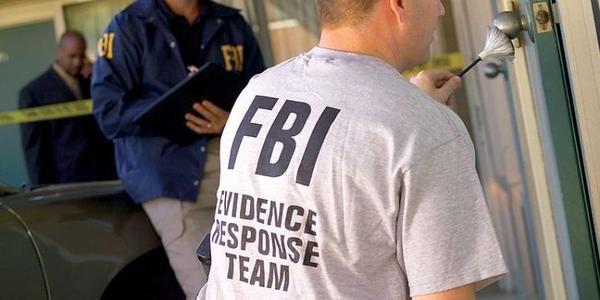 A member of the FBI's Evidence Response Team collects fingerprint evidence. Photo via FBI/Wikimedia.