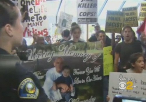 Protestors gathered in the Anaheim Police Department's lobby in July. Screenshot via CBS 2.