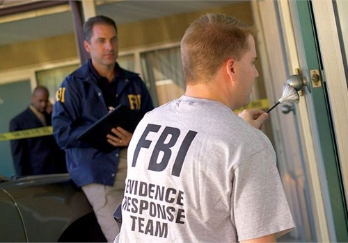 A member of the FBI's Evidence Response Team collects fingerprint evidence. Photo via FBI/Wikimedia.