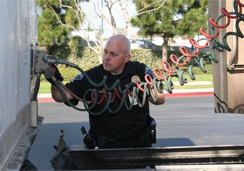 Officer Durling inspects the condition of a 53-foot cargo tractor-trailer's air-brake tubing.Photo courtesy of TPD.