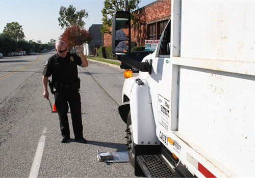 An overweight violation is confirmed as Officer Durling directs a bobtail truck onto his portable truck scale.Photo courtesy of TPD.
