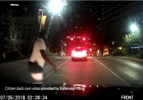 Screen grab of citizen dash-cam video of a man with a gun in Baltimore. Image courtesy of the Baltimore Sun.