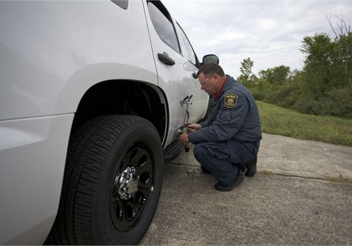 A tester attaches an optical sensor to a Chevy Tahoe to measure top speed and acceleration. Photo: MSP