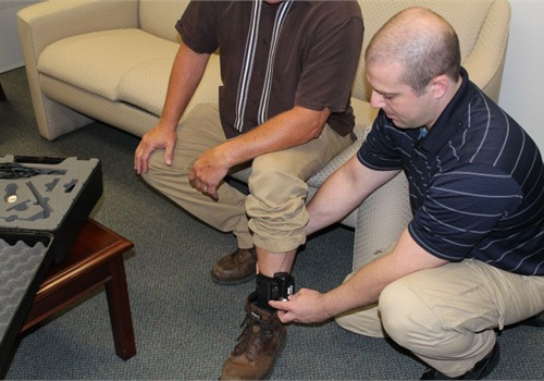 Senior Parole Officer Joseph Leake secures a GPS ankle bracelet on the subject.