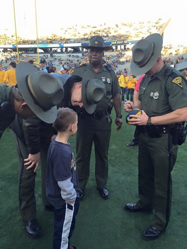 A little boy at a University of West Virginia football game surprised a group of state troopers by asking for their autographs. (Photo: Facebook)