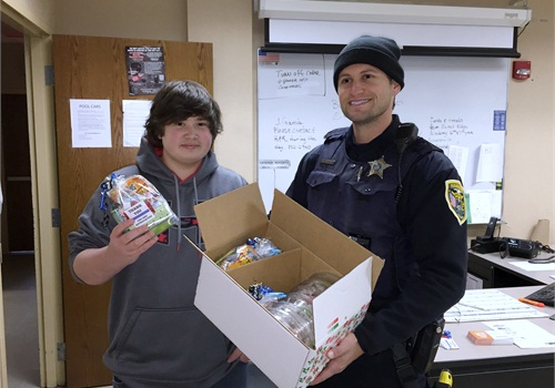 Zachary Witulski presents some gift packages to a Hammond, Ind., officer.