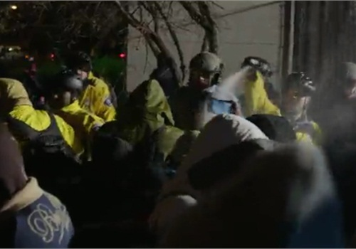 Minneapolis officers use pepper spray on protesters outside of police station. (Photo: Minneapolis Star-Tribune video screenshot)