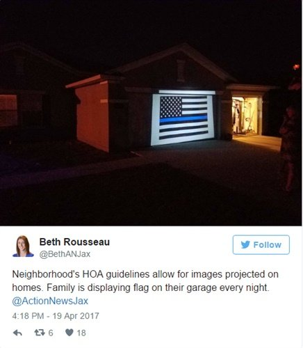 """<p>Twitter post from <a href=""""http://www.actionnewsjax.com/news/local/st-johns-county-family-now-projecting-blue-lives-matter-flag-on-garage/514237736"""">Action News Jax</a> report Beth Rousseau shows projected Blue Lives Matter flag on homeowner's property.</p>"""