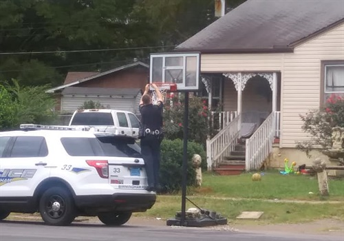A Birmingham officer affixing brand new basketball netting for a hoop in front of a home. Photo: Rhaquel Ryans / Facebook