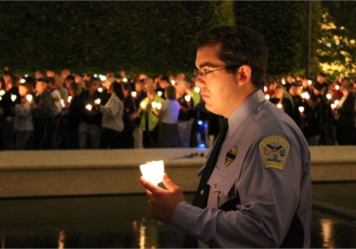A Bismarck (N.D.) Police officer honors the fallen at the 2011 Police Week candlelight vigil. Photo: Paul Clinton