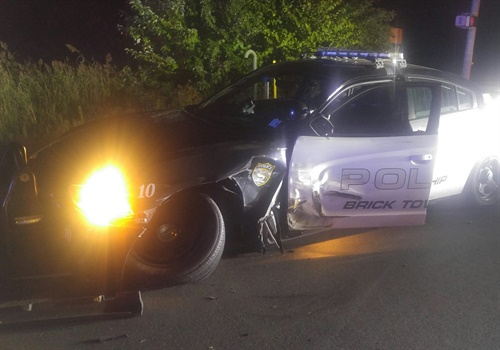 An officer with the Brick Township (NJ) Police Department was assisting with an investigation of a motor vehicle accident when a suspected drunk driver slammed into her parked squad car.  Image courtesy of Brick Township PD / Facebook.