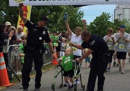 """Officers Tim Wagner and Joe Donovan flanked little Easton Jordan for the duration of the walk as he worked relentlessly to cross the finish line of the""""walk, run, and roll"""" fundraiser to benefit the Make Lemon Aide Foundation for Cerebral Palsy. Image courtesy of Buffalo PD / Facebook."""